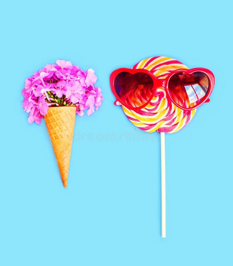 Glasskotten blommar och färgrik klubbakaramell med solglasögon på pinnen över rosa färger royaltyfria foton