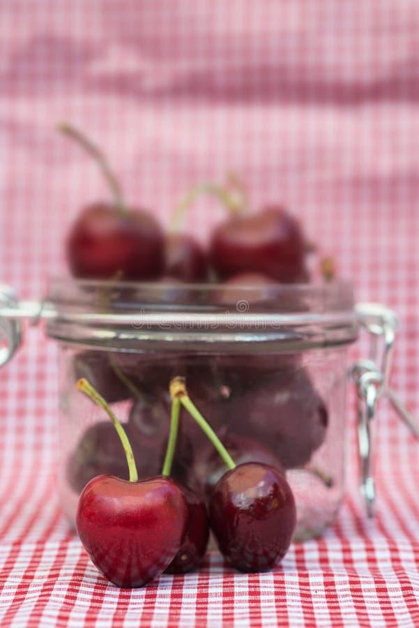 Glasspeicherglas voll frische Kirschen stockfotos