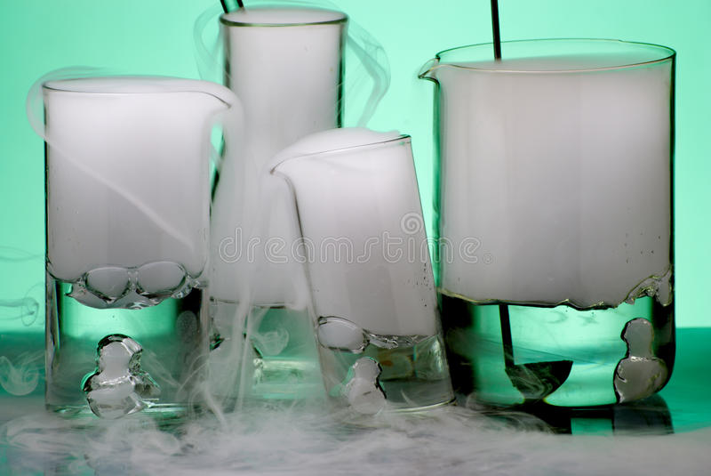 Glassware during experiment with erupted vapors royalty free stock photography
