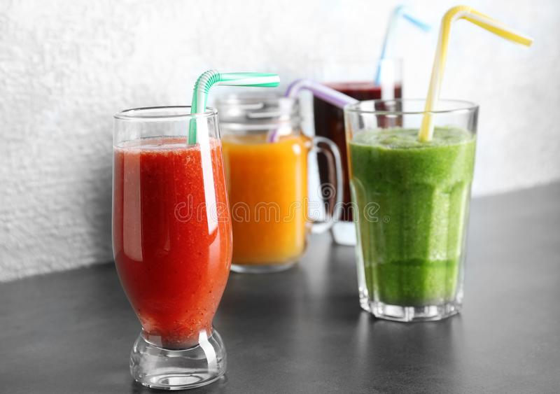 Glassware with smoothies on table against. Light background stock image