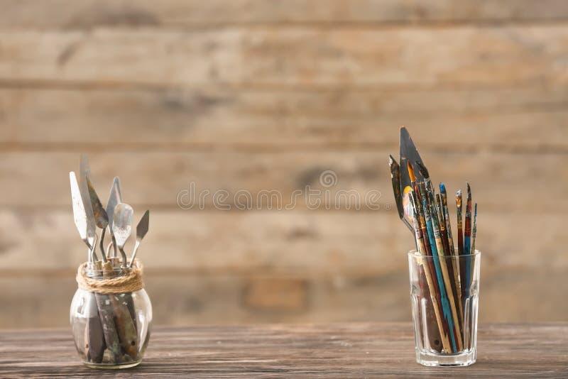 Glassware z farb muśnięciami i paleta nożami na drewnianym stole obraz royalty free