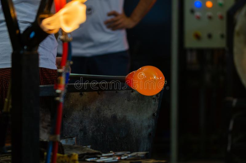 Glassworks glass manufacturing, process of forming a decorative. Molten glass on a rod for glass blowing.She is shaping the glass royalty free stock images