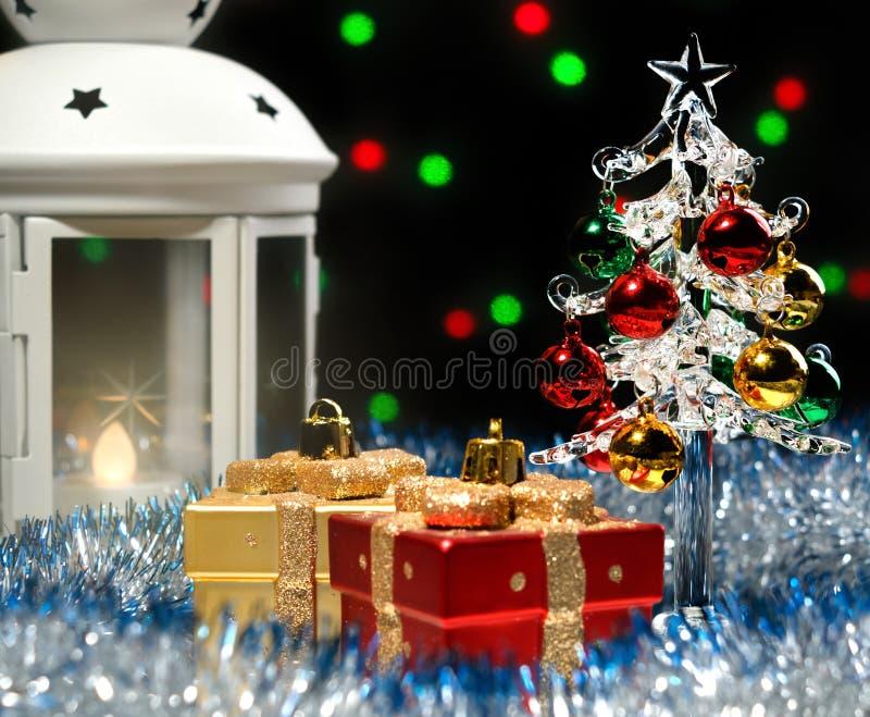Glastannenbaum und weiße Laterne, die im blauen Lametta mit Weihnachtsdekorationen auf Hintergrund mit unscharfen Lichtern steht lizenzfreies stockfoto