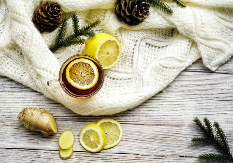 Glastasse tee mit Zitronen- und Ingwerwurzelscheiben, tadelloses Blatt auf Glasuntertasse auf einem rustikalen Holztisch auf Hint lizenzfreie stockfotografie