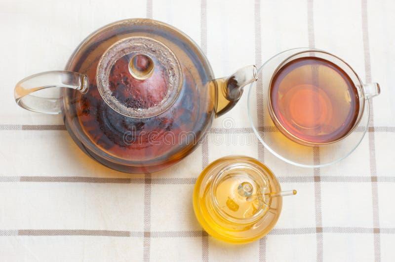 Glasteekanne, Becher, honney Glas stockfoto