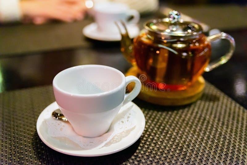 Glasteekanne mit blühendem schwarzem Tee- und weißemschalentabellen- und Dunklemhintergrundstillleben stockfoto