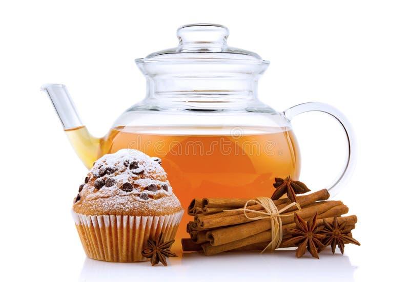 Glasteekanne mit den Gewürzen und Kuchen lokalisiert lizenzfreie stockbilder