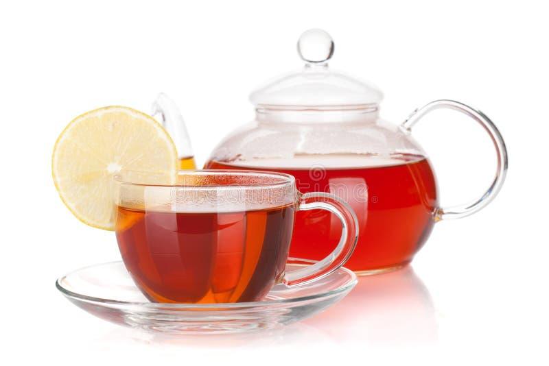 Glasteekanne und Cup schwarzer Tee mit Zitronenscheibe lizenzfreie stockfotografie