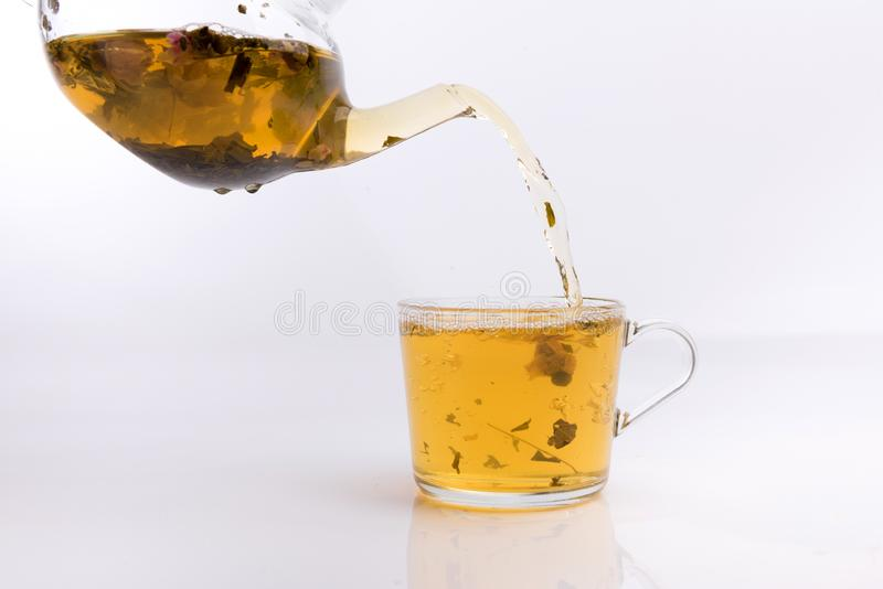 Glastheepot die groene thee gieten in kop op witte achtergrond royalty-vrije stock foto's