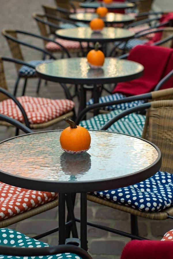 Glastische eines Cafés im Freien mit Kürbisen und farbige Kissen von Stühlen lizenzfreies stockfoto