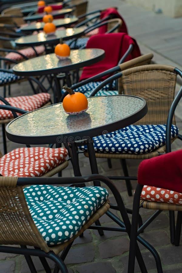 Glastische eines Caf?s im Freien mit K?rbisen und farbige Kissen von St?hlen lizenzfreie stockbilder