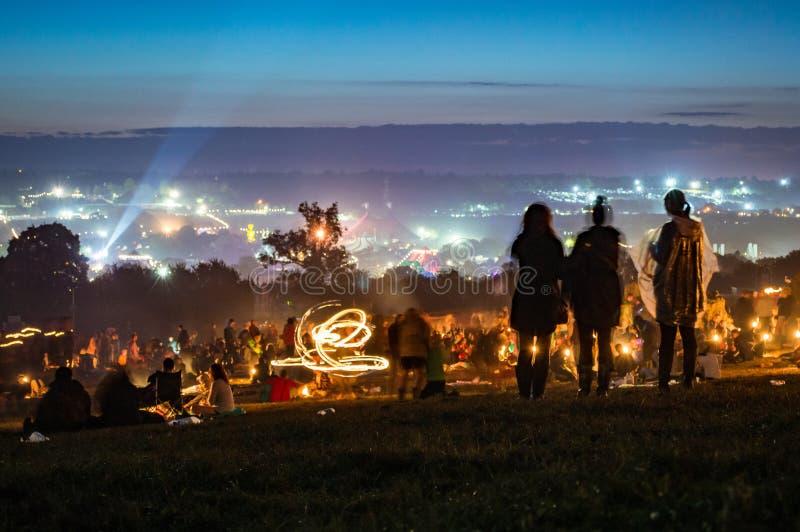 Glastonbury festival 30th Juni 2014 Ung kvinna som tre ser över ljusen och folkmassorna av den Glastonbury festivalen på natten i royaltyfria bilder