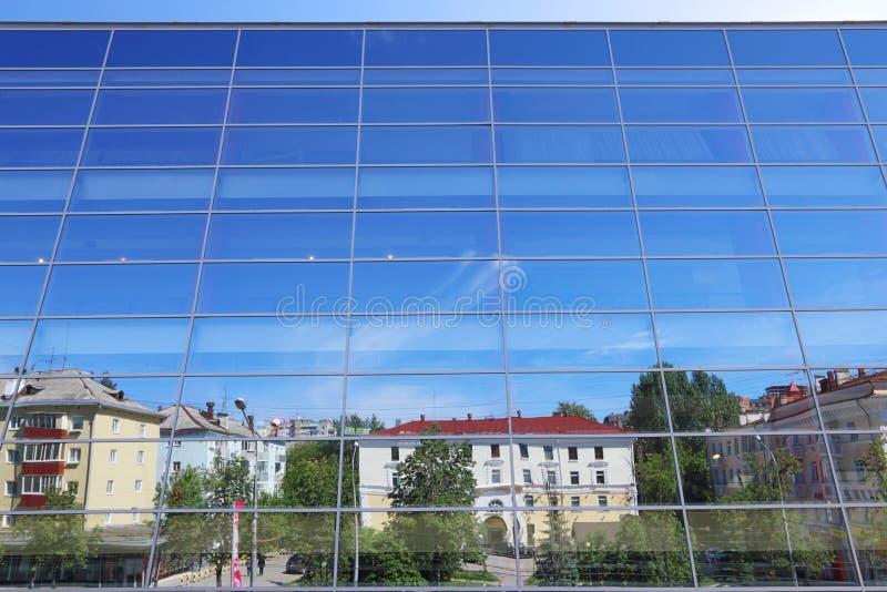 Glasvägg av byggnad med reflexion av blå himmel arkivbild