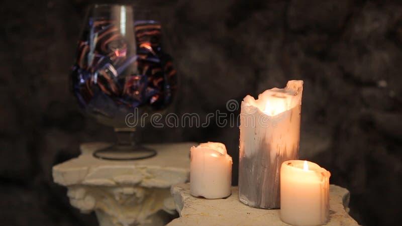 Glasvaas met chocolade en suikergoed en brandende kaarsen in de voorgrond Chocoladesnoepjes in een vaas en het branden stock foto