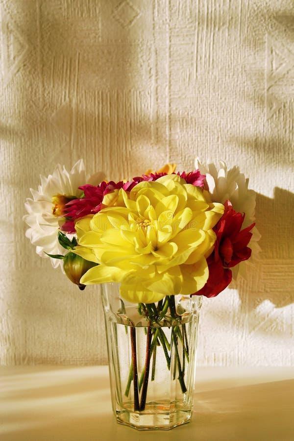 Glasvaas met gele, witte, roze en rode pioenen op de witte lijst royalty-vrije stock foto