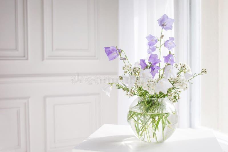 Glasvaas met lilac en witte floweers in licht comfortabel slaapkamerbinnenland Witte muur, zonlicht van venster, exemplaarruimte royalty-vrije stock fotografie