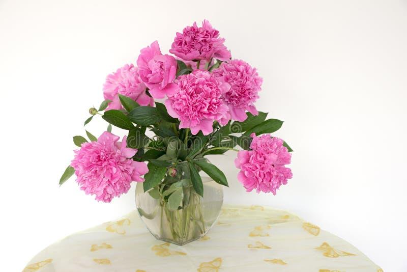 Glasvaas met roze paeony bloemen op een lijst met textiel royalty-vrije stock foto's
