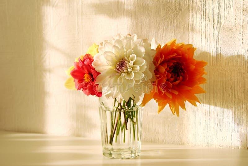 Glasvaas met witte, oranje, rode en gele pioenen op de witte lijst royalty-vrije stock afbeeldingen