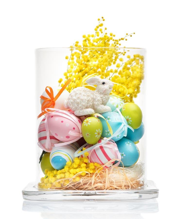 Glasvase mit Ostern-Dekorationen Häschen, gelbe Blumen und Ostereier stockbilder