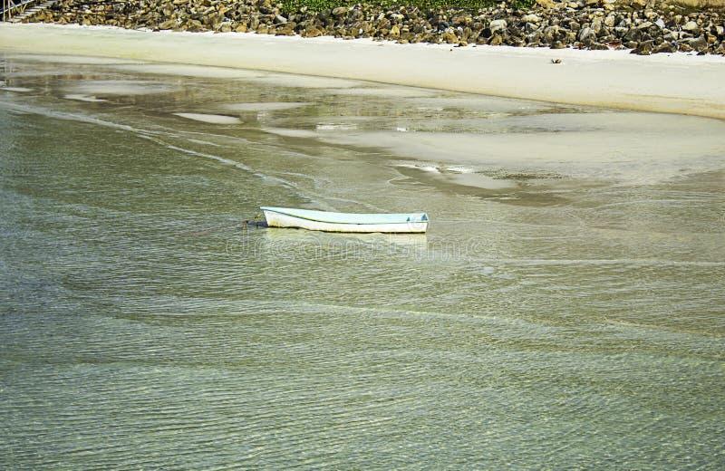 Glasvezelboot die op het Strand en het huisvuil op de rotsen in Koh Phangan, Surat Thani in Thailand wordt geparkeerd stock fotografie