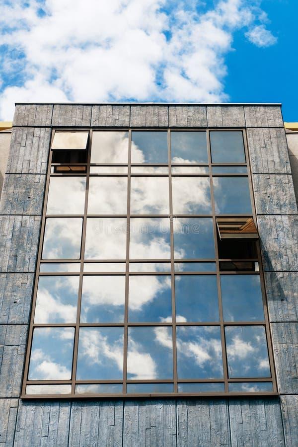 Glasvoorgevel met wolkenbezinningen stock afbeeldingen