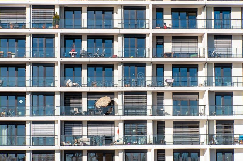 Glasvoorgevel van een modern flatgebouw met heel wat balkons stock afbeelding