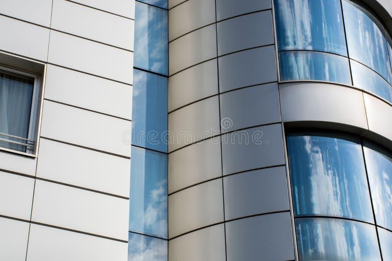 Glaswand des modernen Gebäudes mit Himmel- und Wolkenreflexion in den Fenstern lizenzfreie stockfotos