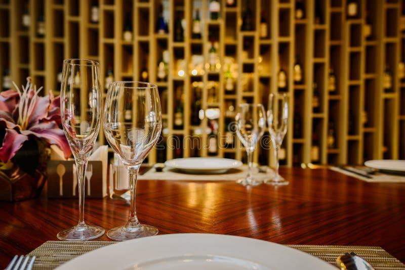 Glaswaren und Tischbesteck auf Speisentabelle im warmen Licht lizenzfreies stockbild