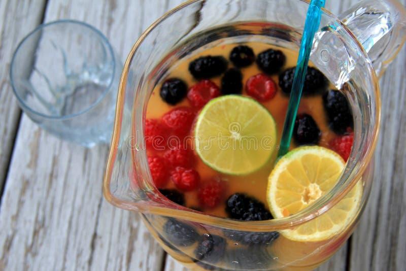 Glaswaterkruik met vers gedrukt sap en gesneden fruit stock foto's