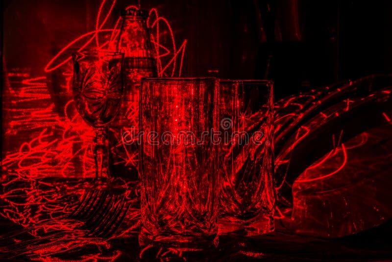 Glaswerk in de keuken in het licht van een rode laser, abstract art. stock afbeelding