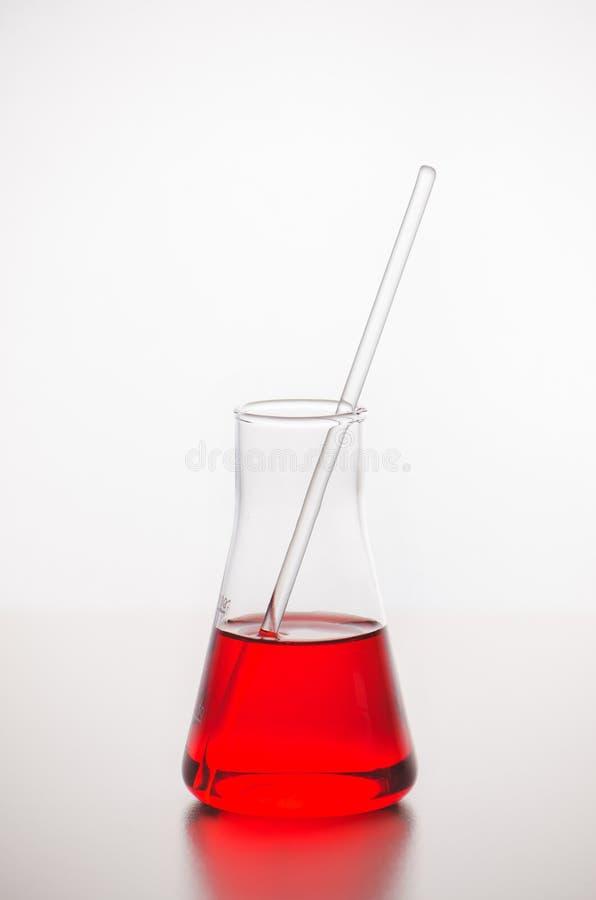 glaswerk Een fles met een rode vloeistof en een glasstaaf LABORATORIUManalyse T stock foto