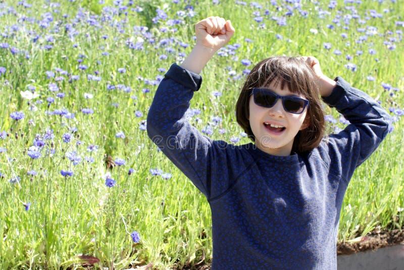 Glat barn med blå solglasögon som skrattar för att vara i natur royaltyfri fotografi