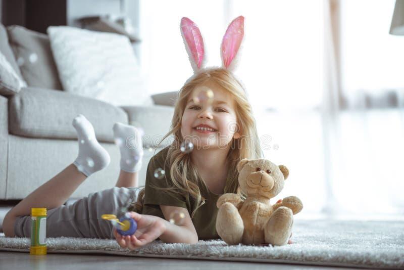 Glat barn som har gyckel med hemmastadda leksaker royaltyfri foto