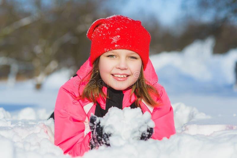 Glat barn som spelar i snö Lycklig flicka som har rolig utvändig vinterdag arkivbild