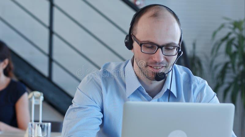 Glat call centermedel med hans hörlurar med mikrofon som talar se bärbara datorn arkivbild