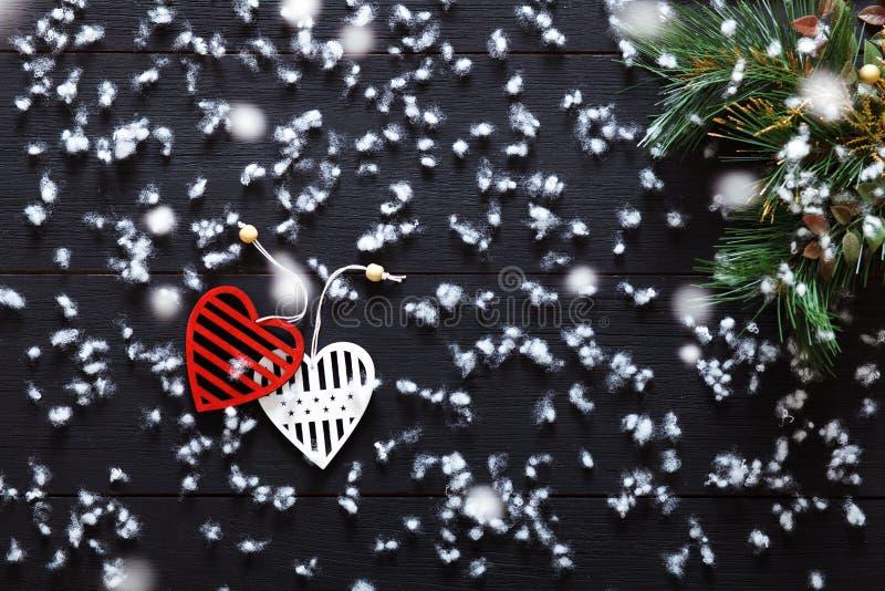 Glat julpynt, snöflingor, vita röda hjärtor och grönt xmas-träd på det svarta träbakgrundskortet, bästa sikt royaltyfri fotografi