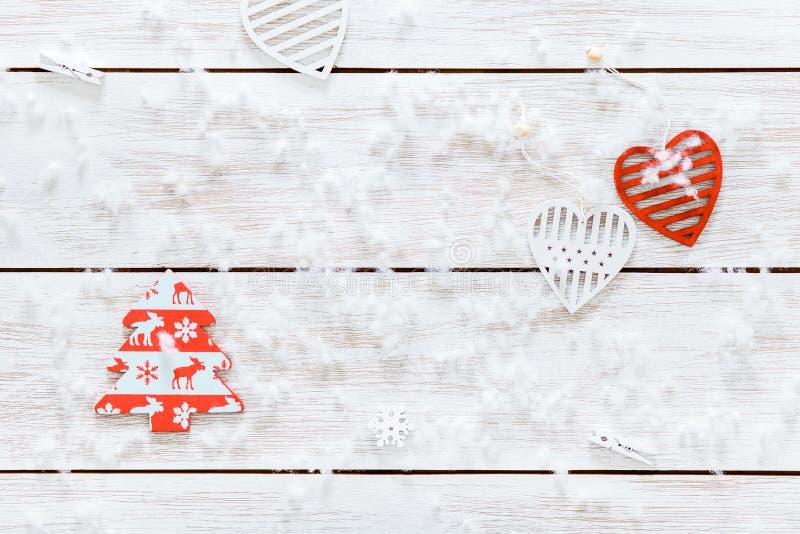Glat julpynt, snöflingor, vita röda hjärtor och leksakxmas-träd på det ljusa träbakgrundskortet, bästa sikt fotografering för bildbyråer