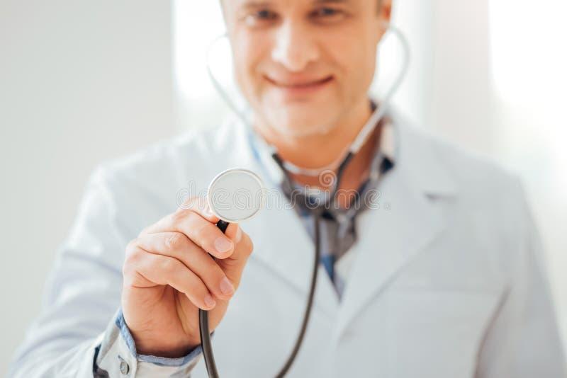 Glat kompetent läkareanseende och innehav hans statoscope royaltyfri fotografi