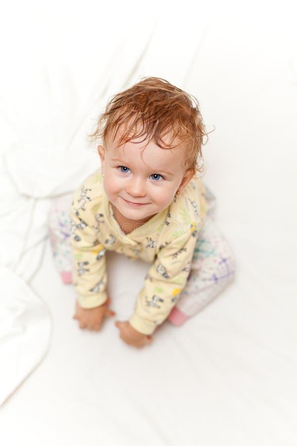 Glat liten flickasammanträde på säng och se upp på kameran arkivbilder