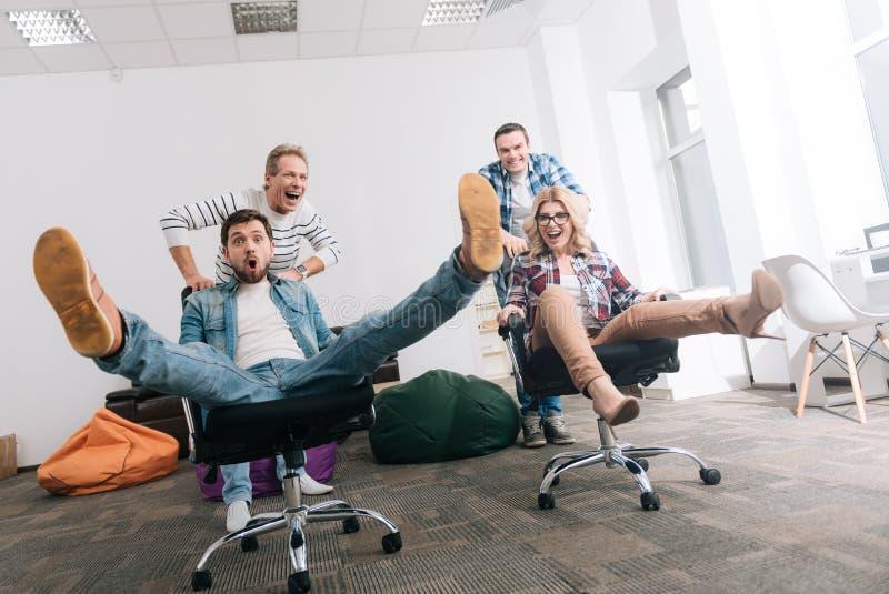 Glat lyckligt folk som rider i kontorsstolarna arkivfoto
