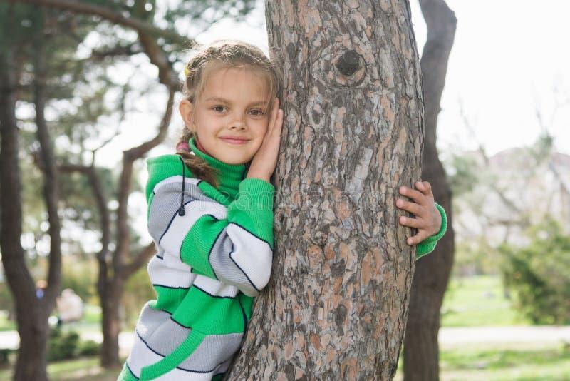 Glat sju-år gammalt flickasammanträde på en trädstam i den tidiga våren arkivbild