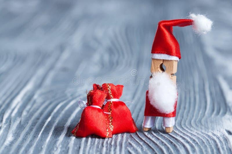 Glatt julinbjudankort Den roliga jultomten för leksakklädnypapinne med den röda gåvan hänger löst på härlig träbakgrund Makro royaltyfri fotografi