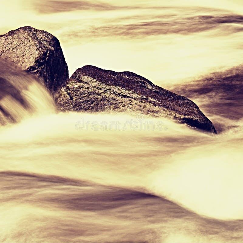 Glatte Flusssteine im Gebirgsstrom Klares Wasser verwischt durch lange Belichtung, Niedrigwasserniveau stockfoto