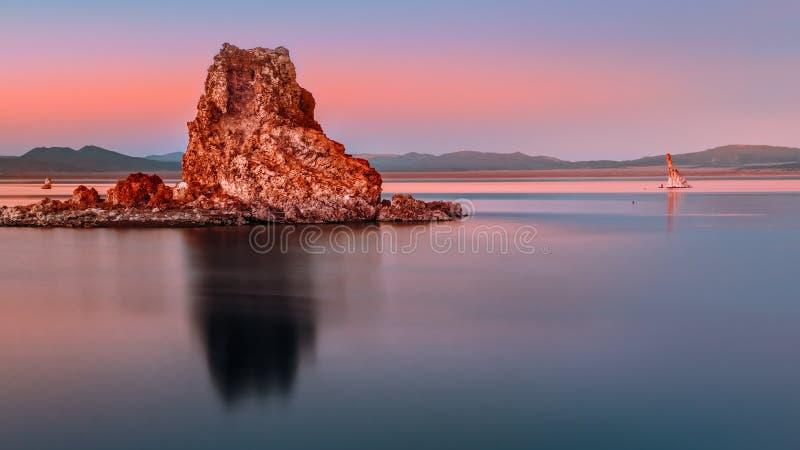 Glatte Reflexion eines großen Felsens mit Bergen im Hintergrund lizenzfreies stockfoto