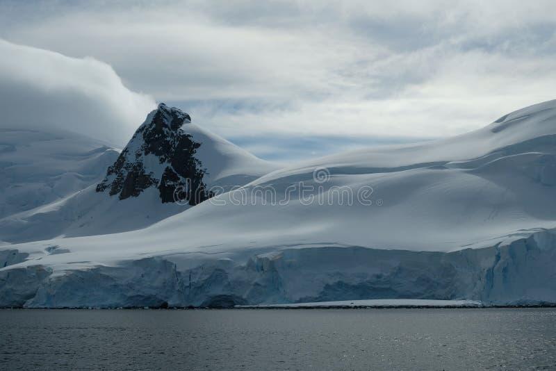 Glatte schneebedeckte Berge der Antarktis am bewölkten Tag stockfotografie
