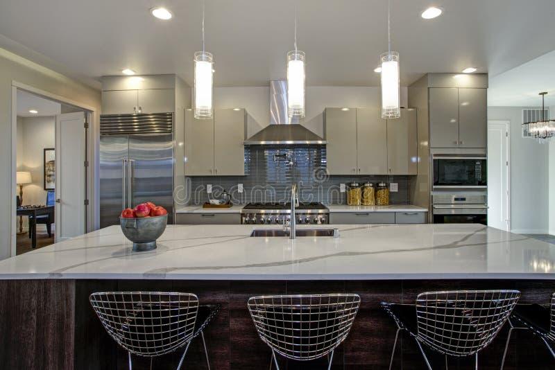 Glattes modernes Küchendesign mit einer grauen Mittelinsel stockfotografie