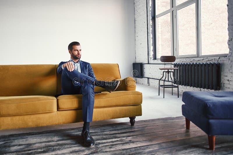 Glauben entspannt Hübscher und stilvoller junger Geschäftsmann steht auf Sofa still und denkt an Geschäftsideen lizenzfreie stockfotografie