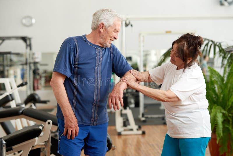 Glaubende Schmerz des älteren Mannes im Ellbogen während des Trainings lizenzfreie stockfotos