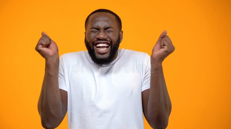 Glaubendes Gl?ck des jungen afroen-amerikanisch Mannes, Lottogewinner, gelber Hintergrund lizenzfreie stockbilder