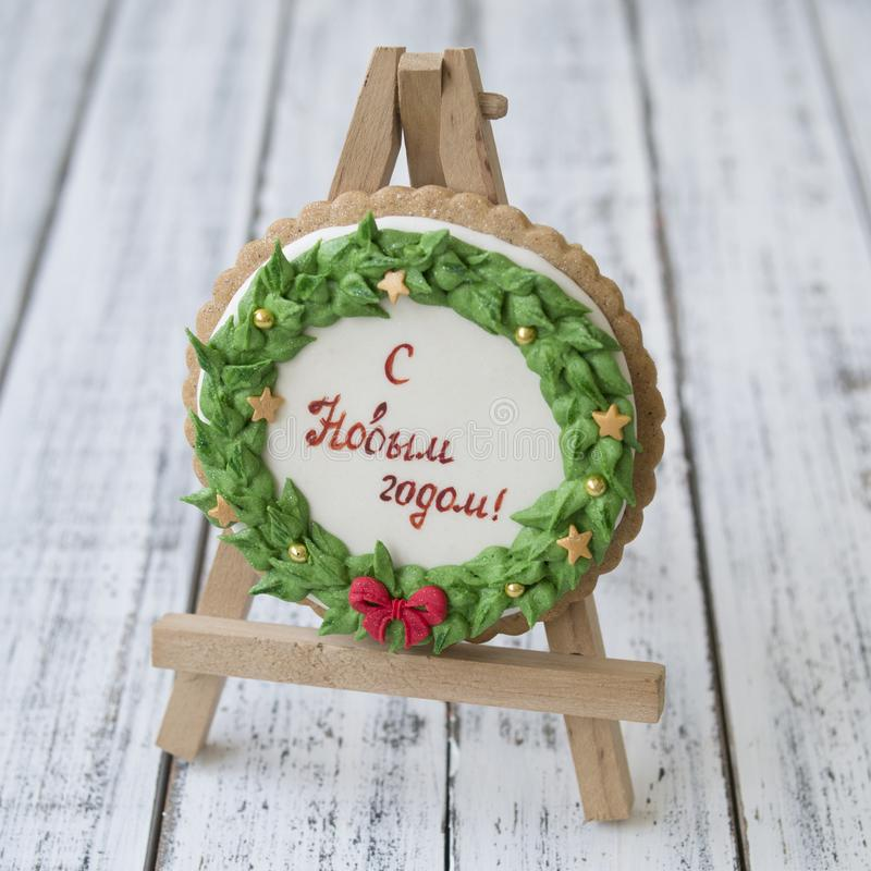 A glaze Christmas gingerbread cookie in the form of a Christmas wreath with a red bow and golden stars with inscription in Russian royalty free stock photo